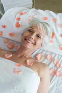 Senior woman covered in petals on bedの写真素材 [FYI03649986]