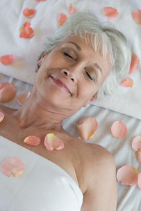 Senior woman covered in petals on bedの写真素材 [FYI03649989]