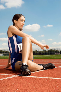 Female athlete stretching on running trackの写真素材 [FYI03650028]