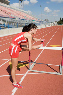 Female athlete stretching on hurdleの写真素材 [FYI03650063]