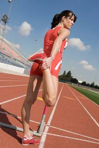Female athlete stretching on hurdleの写真素材 [FYI03650064]
