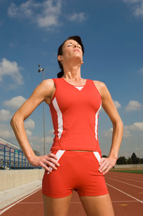 Female track athlete standing on trackの写真素材 [FYI03650107]