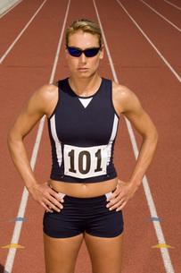 Female track athlete standing on trackの写真素材 [FYI03650127]