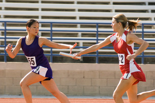 Female track athlete passing relay baton to another oneの写真素材 [FYI03650132]
