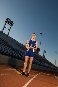 Female track standing on track holding relay batonの写真素材 [FYI03650136]