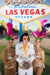 Female dancers and Elvis impersonator posing in front of Las Vegas welcome sign Nevada USAの写真素材 [FYI03650172]