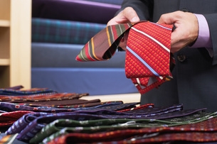 Businessman selecting ties in clothes store mid sectionの写真素材 [FYI03650184]
