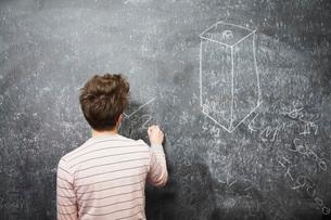 Young man writing on blackboard back viewの写真素材 [FYI03650196]
