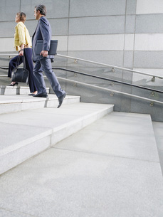 Business people walking up steps outdoors side viewの写真素材 [FYI03650238]