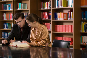 Young man and woman studying at desk in libraryの写真素材 [FYI03650294]