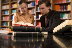 Young man and woman studying at desk in library focus on books in foregroundの写真素材 [FYI03650295]