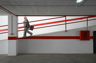 Two businessmen walking down ramp in parking garageの写真素材 [FYI03650309]