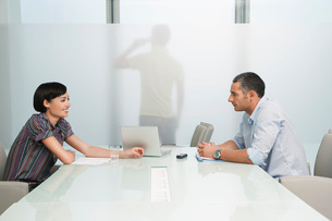 Man and woman talk over conference table man on mobile phone visible through translucent office wallの写真素材 [FYI03650319]