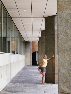 Woman stretching against a pillarの写真素材 [FYI03650355]