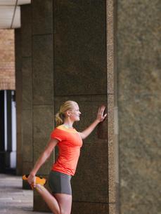 Woman stretching against a pillarの写真素材 [FYI03650356]