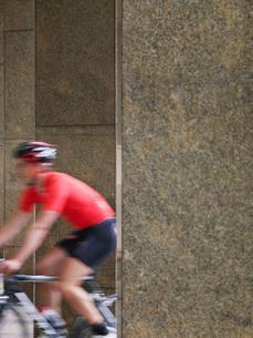 Man cycling between pillars motion blurの写真素材 [FYI03650357]