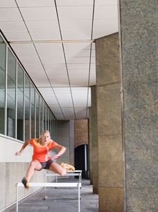Woman jumping hurdles outside buildingの写真素材 [FYI03650364]