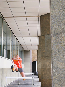 Woman jumping hurdles outside buildingの写真素材 [FYI03650365]