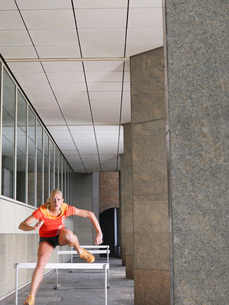 Woman jumping hurdles outside buildingの写真素材 [FYI03650367]