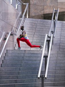 Male athlete stretching on staircase outside buildingの写真素材 [FYI03650369]