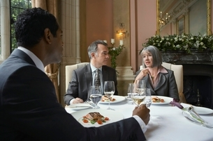Three business people sitting at restaurant table talkingの写真素材 [FYI03650386]
