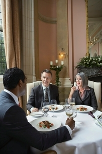 Three business people sitting at restaurant table talkingの写真素材 [FYI03650387]