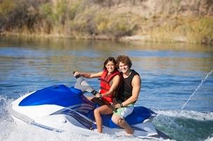 Young couple riding jetski on lake portraitの写真素材 [FYI03650408]