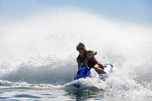 Young man riding jetski on lakeの写真素材 [FYI03650411]