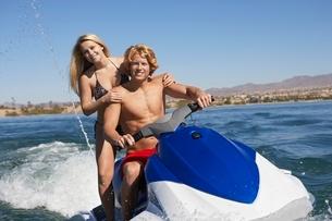 Young couple riding jetski on lake portraitの写真素材 [FYI03650432]