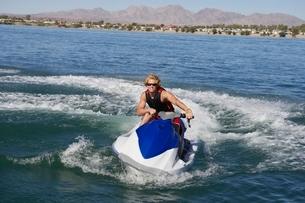 Young man riding jetski on lakeの写真素材 [FYI03650433]