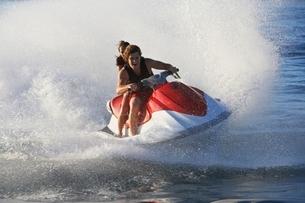 Young couple riding jetski on lakeの写真素材 [FYI03650439]