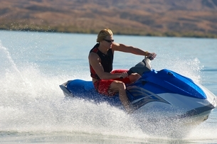 Young man riding jetski on lakeの写真素材 [FYI03650442]