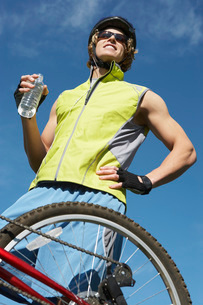Male cyclist holding water bottle outdoorsの写真素材 [FYI03650467]