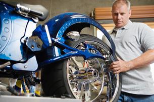 Mid-adult mechanic repairing motorcycleの写真素材 [FYI03650545]