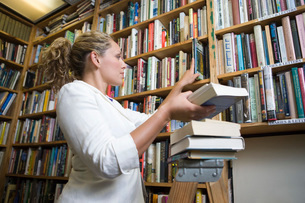 Female librarian putting books on shelvesの写真素材 [FYI03650554]