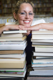 Portrait of female librarian with stacked booksの写真素材 [FYI03650558]