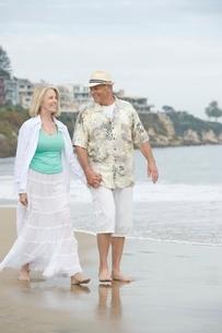 Senior couple walk holding hands on beachの写真素材 [FYI03650589]