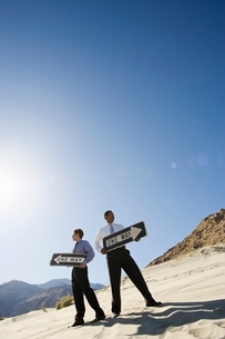 Two Businessmen Holding One Way Signs in the Desertの写真素材 [FYI03650619]