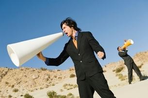 Two Businessmen Using Megaphones in Desertの写真素材 [FYI03650633]