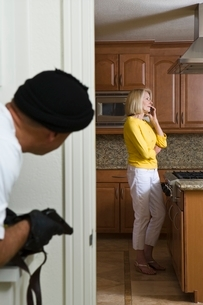 Burglar holding gun approaches woman on phone in kitchenの写真素材 [FYI03650736]