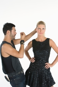 Hair stylist makes adjustments to model standing with hands on hipsの写真素材 [FYI03650754]