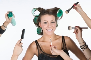 Woman in rollers  with cosmetics products on handの写真素材 [FYI03650755]