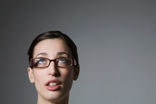 Brunette with blue eyes and spectacles looking upの写真素材 [FYI03650761]