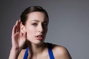 Brunette with hand behind earの写真素材 [FYI03650765]