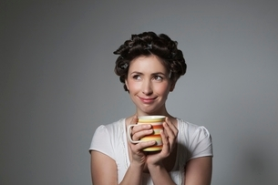 Coy young woman with hair curlers holding cupの写真素材 [FYI03650770]