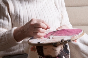 Elderly woman sits working on needlepointの写真素材 [FYI03650798]
