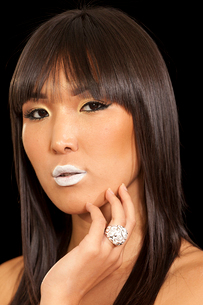 Woman posing on black background wearing beautiful ring with white lipstickの写真素材 [FYI03650822]