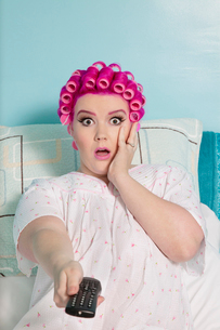 Portrait of shocked woman holding remote with hair curlers sitting on bedの写真素材 [FYI03650827]