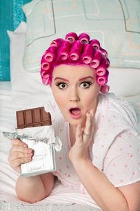 Portrait of shocked woman with chocolate lying on bedの写真素材 [FYI03650843]