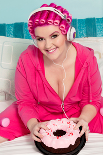 Portrait of a happy young woman wearing headphones sitting on bed with cakeの写真素材 [FYI03650855]